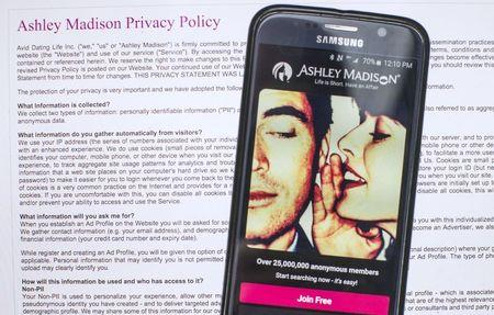 A photo illustration shows the privacy policy of the Ashley Madison website seen behind a smartphone running the Ashley Madison app in Toronto, August 20, 2015.  REUTERS/Mark Blinch