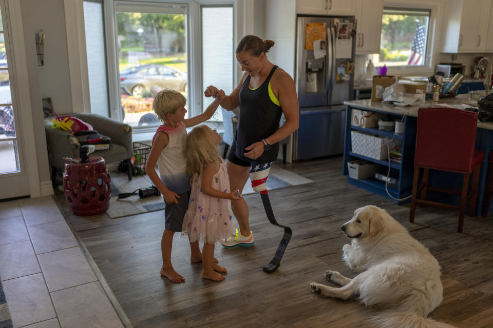 """Melissa Stockwell plays with her children, Dallas and Millie, in their home in Colorado Springs, Colo., on Saturday, Aug. 7, 2021. """"I've always been an optimistic person,"""" she says. """"Probably annoyingly optimistic to lots of people."""" (AP Photo/Emilio Morenatti)"""