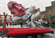 A political carnival float depicting Russia's President Vladimir Putin fighting with opposition Alexei Navalny is rolled out to be shown in the streets in Duesseldorf, Germany, Monday, Feb. 15, 2021. Because of the coronavirus pandemic the traditional; carnival parades are canceled but eight floats are pulled through the empty streets in Duesseldorf, where normally hundreds of thousands of people would celebrate the street carnival. (AP Photo/Martin Meissner)