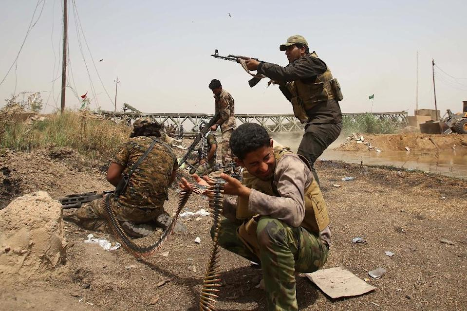 A member of the Popular Mobilisation units opens fire at Islamic State group militants in the area of Sayed Ghareeb, near Dujail, some 70 kilometres north of Baghdad, on May 28, 2015 (AFP Photo/Mohammed Sawaf)