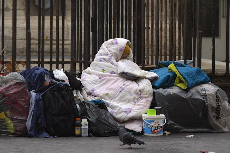 A homeless woman is wrapped in a blanket on a street in Paris, France, on December 3, 2014 (AFP Photo/Joel Saget)