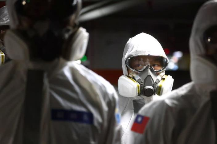 Soldiers prepare to spray disinfectant at the Taoyuan General Hospital in Taoyuan
