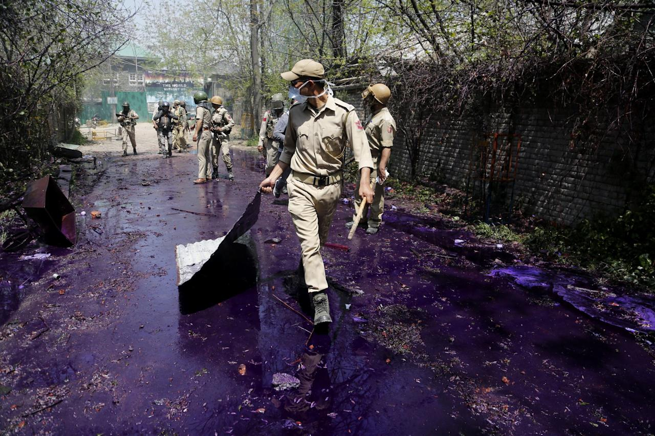 <p>An Indian policeman removes a metal sheet used by protesting students as a shield as colored water used by police to disperse them fails the ground after a clash in Srinagar, Kashmir. The clashes on Monday began in Srinagar when hundreds of college students took to the streets to protest a police raid in a college in southern Pulwama town over the weekend, in which at least 50 students were injured. (AP Photo/Mukhtar Khan) </p>