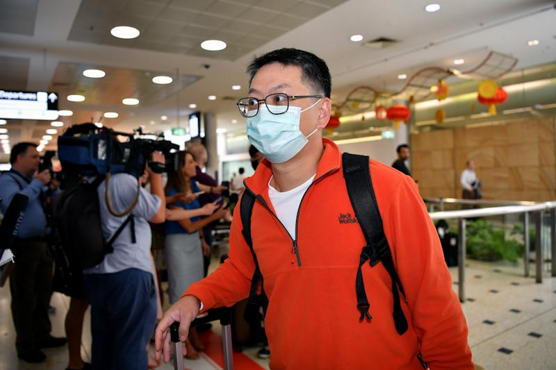 A passenger wearing a protective mask on arrival at Sydney International Airport in Sydney on Thursday. Source: AAP Image/Joel Carrett
