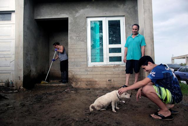 <p>A family is seen in their front yard flooded with mud, after the island was hit by Hurricane Maria in Toa Baja, Puerto Rico, Oct. 16, 2017. (Photo: Alvin Baez/Reuters) </p>