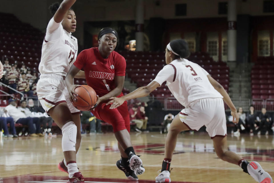 Louisville guard Dana Evans (1) drives to the basket between Boston College forward Taylor Soule (13) and guard Jaelyn Batts (3) during the first half of an NCAA college basketball game Thursday, Jan. 16, 2020, in Boston. (AP Photo/Elise Amendola)