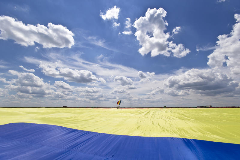 A man holding a Romanian flag stands on a record breaking version of the flag, on the Clinceni Airfield, south of Bucharest, Romania, Monday, May 27, 2013. Romania entered the Guinness Book of records after it unveiled the largest flag ever made. It took about 200 people several hours Monday to unfurl a five-ton flag of Romania which organizers said measured 349.4 meters by 226.9 meters, about three times the size of a football pitch.(AP Photo/Vadim Ghirda)