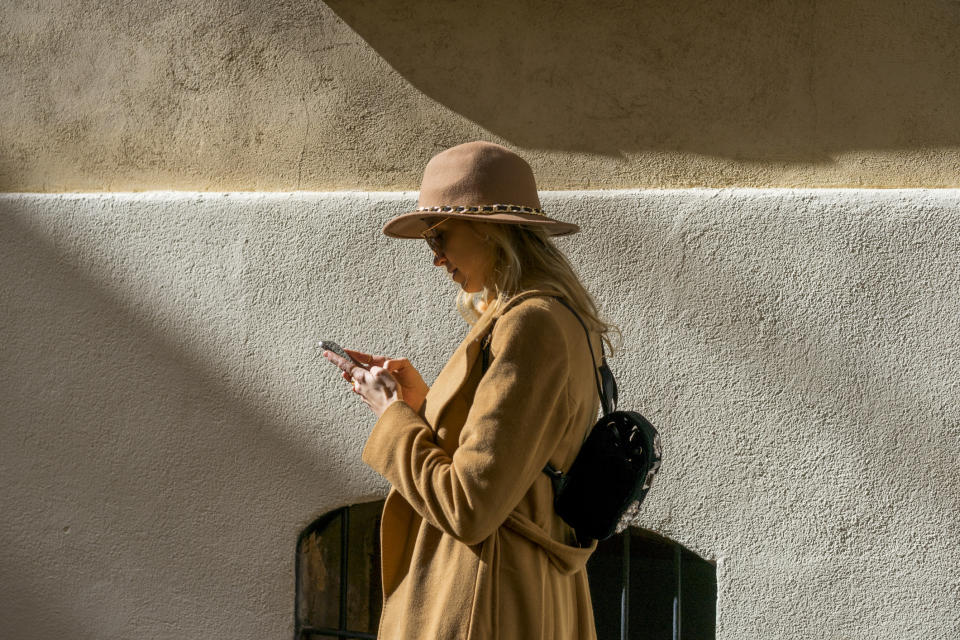 Fashionable young woman at a building using cell phone. (PHOTO: Getty Images)
