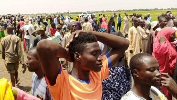People watch as rescuers search for survivors in the River Niger after a boat capsized