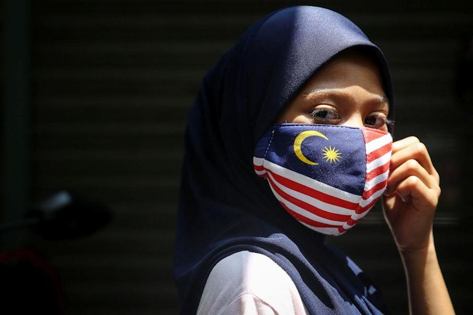 A woman wearing a mask in the design of the Jalur Gemilang is pictured in Kuala Lumpur August 16, 2020. — Picture by Yusof Mat Isa