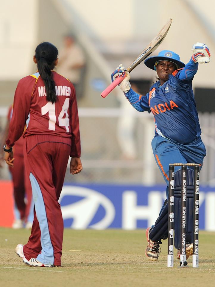 West Indian cricketer Anisa Mohammed (L) looks on as Indian cricketer Thirush Kamini celebrates her century during the inaugural match of the ICC Women's World Cup 2013 between India and West Indies at the Cricket Club of India's Brabourne stadium in Mumbai on January 31, 2013.     AFP PHOTO/Indranil MUKHERJEE        (Photo credit should read INDRANIL MUKHERJEE/AFP/Getty Images)