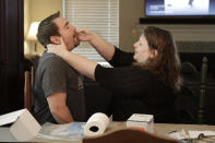 Mendy McNulty swabs the nose of her husband, Joe, in their home in Mount Juliet, Tenn., Tuesday, July 28, 2020. The family is participating in testing done twice a month to help answer some of the most vexing questions about the coronavirus. (AP Photo/Mark Humphrey)