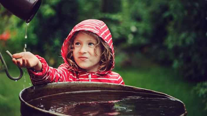Young girl catching water from gutter