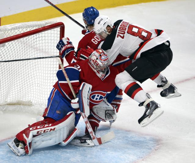 New Jersey Devils right wing Dainius Zubrus (8) jumps in front of Montreal Canadiens goalie Carey Price (31) and Montreal Canadiens defenseman Josh Gorges (26) during second period National Hockey League action, Tuesday, Jan. 14, 2014, in Montreal. (AP Photo/The Canadian Press, Ryan Remiorz)