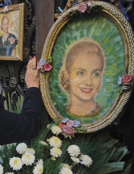 """A woman touches the tomb of Argentina's late former first lady Maria Eva Duarte de Peron, better known as """"Evita,"""" at a cemetery in Buenos Aires, Argentina, Thursday, July 26, 2012. Argentines commemorate the 60th anniversary of the death of their most famous first lady on Thursday. Evita died of cancer on July 26, 1952 at the age of 33. (AP Photo/Sergio Goya)"""