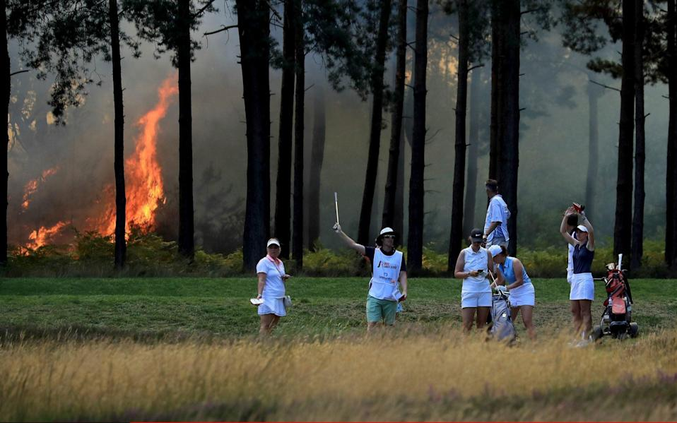 A heath fire behind the tenth tee stops play as the group of Cara Gainer, Sophie Powell and Gabriella Cowley wait to play off during day three of The Rose Ladies Series on The West Course at Wentworth Golf Club