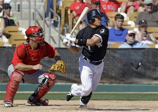 Chicago White Sox's Kosuke Fukudome, from Japan, singles in the fifth inning of a spring training baseball game as Los Angeles Angels catcher Chris Iannetta, right, watches on Wednesday, March 14, 2012, in Glendale, Ariz. (AP Photo/Mark Duncan)