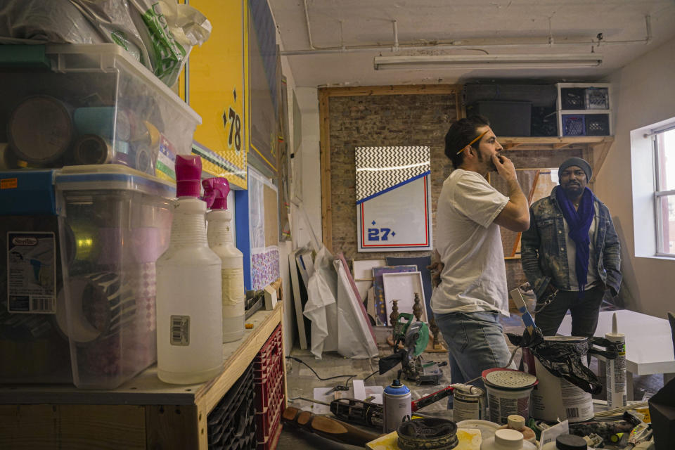Painter Guy Stanley Philoche, a 43-year-old Haitian immigrant and star in the New York art world, visits his studio neighbor fellow artist Michael Shannon, Thursday Nov. 19, 2020, in New York. After a hugely successful gallery show, Philoche wanted to treat himself to a fancy $15,000 watch, instead he bought the works of fellow artists struggling in the pandemic, including an abstract mixed-media piece by Shannon. (AP Photo/Bebeto Matthews)