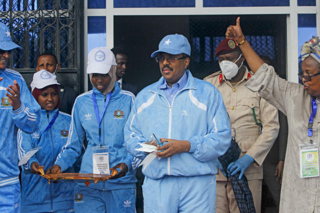 Somalia's President Mohamed Abdullahi Mohamed, center, prepares to cut the ribbon for the reopening of the stadium in Mogadishu, Somalia Tuesday, June 30, 2020. At least three mortar blasts struck the Mogadishu Stadium Tuesday evening, just hours after it was reopened by Somalia's President Mohamed Abdullahi Mohamed, who had left before the shells hit, following years of instability. (AP Photo/Farah Abdi Warsameh)