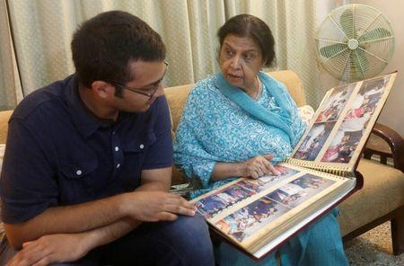 Rehana Khursheed Hashmi, 75, migrated from India with her family in 1960 and whose relatives, live in India, speaks with her grandson Zain Hashmi, 19 while looking family photo album at her residence in Karachi, Pakistan August 7, 2017. REUTERS/Akhtar Soomro