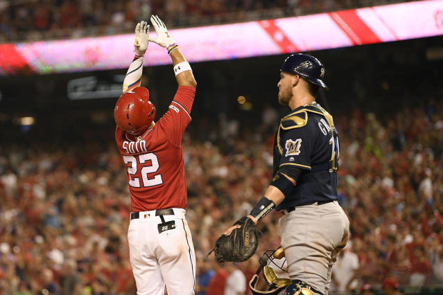 Washington Nationals' Juan Soto (22) celebrates his two-run home run during the third inning of a baseball game, next to Milwaukee Brewers catcher Yasmani Grandal on Saturday, Aug. 17, 2019, in Washington. (AP Photo/Nick Wass)