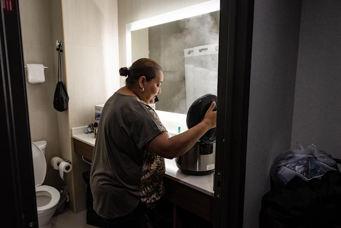 """<span class=""""s1"""">Jenyffer Ortiz cooks chicken in a rice cooker in the hotel bathroom, where there is counter space. She cooks for herself to better deal with diabetes and other ailments. (Photo: David """"Dee"""" Delgado for Yahoo News)</span>"""