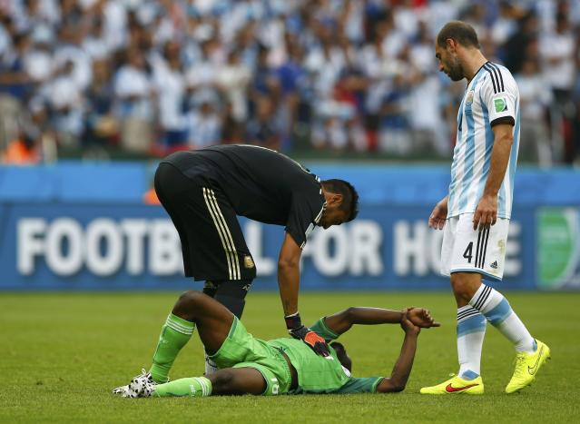Nigeria's Michael Babatunde holds his wrist in pain after being hit with a shot from teammate Ogenyi Onazi, as Argentina's Pablo Zabaleta watches, during the 2014 World Cup Group F soccer match between Argentina and Nigeria at the Beira Rio stadium in Porto Alegre June 25, 2014. REUTERS/Darren Staples (BRAZIL - Tags: SOCCER SPORT WORLD CUP)