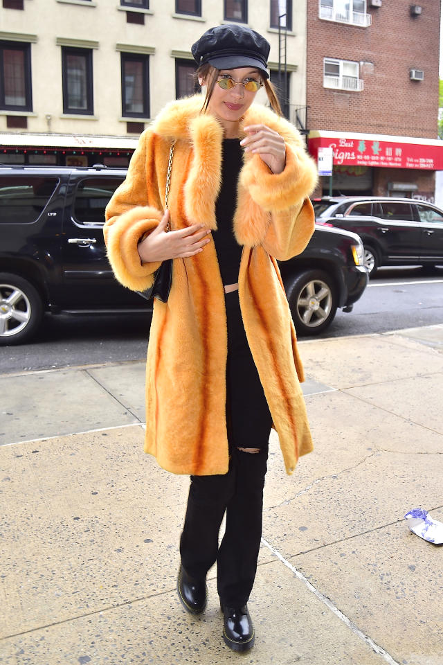 <p>In an citrus colored fur coat with a black top, flared jeans, Dr. Martens boots, round mirrored sunglasses, and a black hat while out in New York City.  </p>