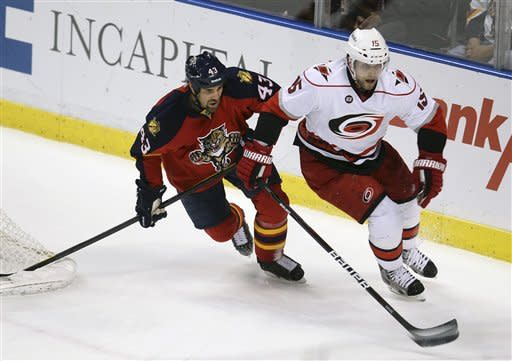 Florida Panthers' Mike Weaver (43) and Carolina Hurricane's Tuomo Ruutu (15) chase the puck during the first period of a NHL hockey game in Sunrise, Fla., Saturday, April 7, 2012. (AP Photo/J Pat Carter)