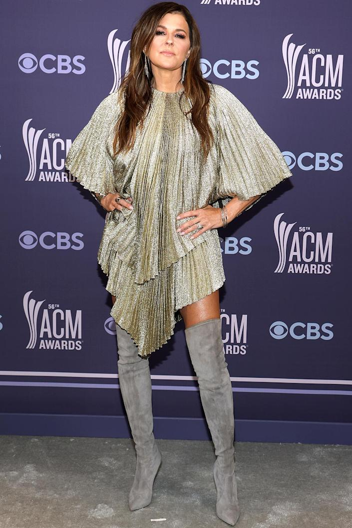 <p>shines in a pleated Stella McCartney mini dress, teamed with over-the-knee boots and drop earrings.</p>