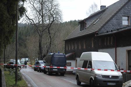 Police cars are parked in Gimmlitztal near the town of Hartmannsdorf-Reichenau, south of Dresden, November 29, 2013. A German policeman has been arrested after the chopped-up body of a man he met on a fetishist website for cannibalism was found buried in his garden, police in the eastern city of Dresden said on Friday. REUTERS/Pawel Sosnowski