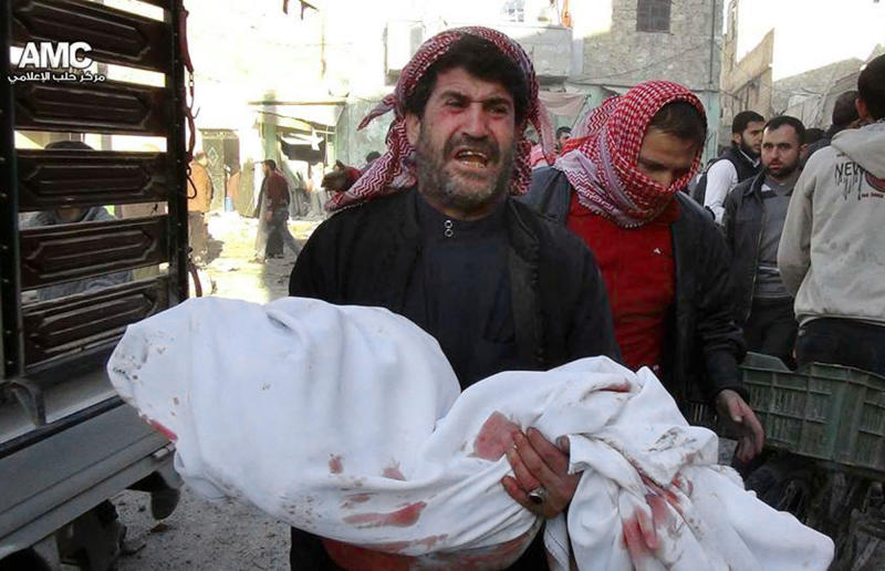 This citizen journalism image provided by Aleppo Media Center AMC which has been authenticated based on its contents and other AP reporting, a Syrian man mourns as he carries the body of a child who was killed following a Syrian government airstrike at the neighborhood of Marjeh in the northern city of Aleppo, Syria, Monday, Dec. 23, 2013. Syrian government forces widened a bombing campaign in rebel-held areas of northern Syria on Monday, striking one of the main border towns near Turkey and killing several people, said activists. (AP Photo/Aleppo Media Center AMC)
