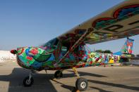 A two-seater Cessna aircraft painted with Pakistani truck art is seen at Jinnah International Airport in Karachi