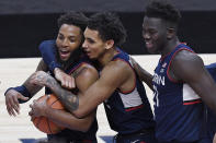 Connecticut's James Bouknight, center, and Adama Sanogo, right, celebrate with R.J. Cole after Cole gained possession of the ball as the clock ran out at the end of an NCAA college basketball game against Southern California, Thursday, Dec. 3, 2020, in Uncasville, Conn. (AP Photo/Jessica Hill)