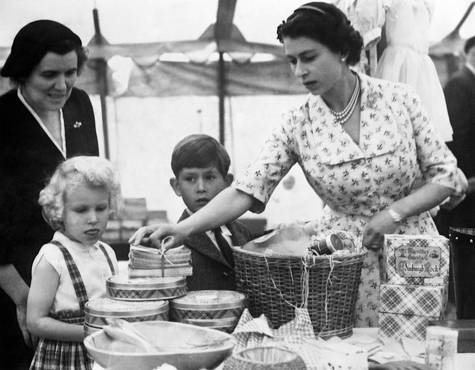 Prince Charles and Princess Anne watch with interest as their mother, the Queen, unpacks a basket of goods onto the stall in which she was serving in a sale of work at Abergeldie Castle, near Balmoral, Scotland. The sale was organised by the Queen Mother to help raise funds for building a vestry at Crathie Church, where the Royal family worship when they stay at Balmoral. Princess Margaret, the Duke of Edinburgh and the Duke of Kent also helped at the sale.   (Photo by PA Images via Getty Images)