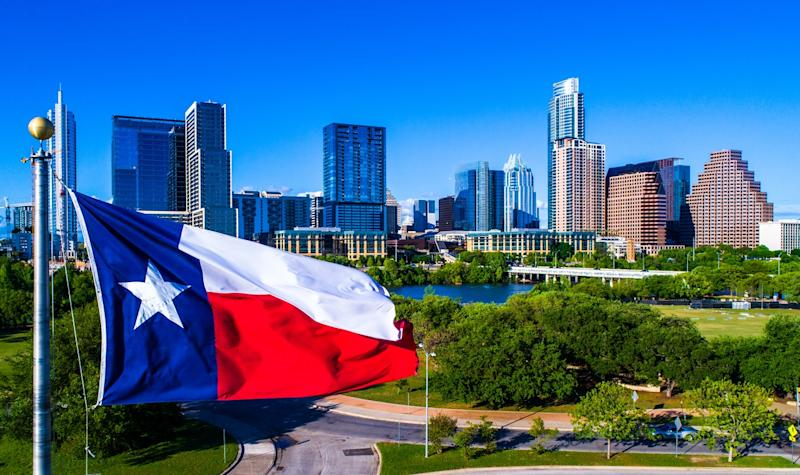 Texas flag flying in front of the Austin skyline.