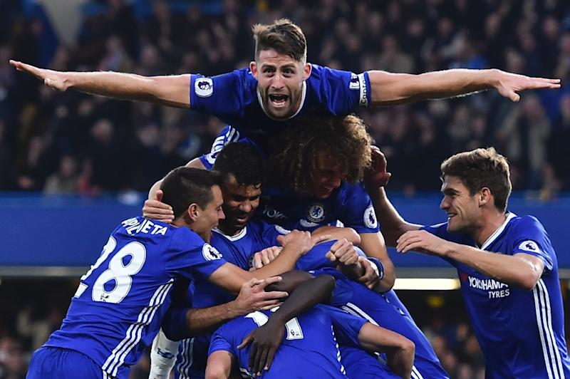 Chelsea's defender Gary Cahill (top) jumps onto the huddle after midfielder N'Golo Kante scored their fourth goal against Manchester United on October 23, 2016