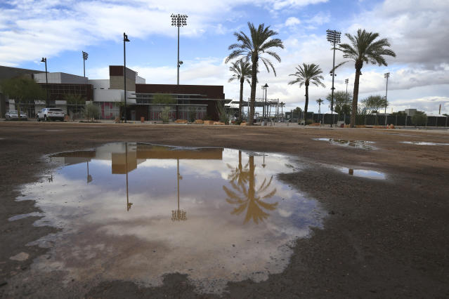 A puddle in an empty parking lot reflects a closed Goodyear Ballpark, home of the Cleveland Indians and Cincinnati Reds baseball teams, Thursday, March 12, 2020, in Goodyear, Ariz. Major League Baseball has suspended the rest of its spring training game schedule because if the coronavirus outbreak. MLB is also delaying the start of its regular season by at least two weeks. (AP Photo/Ross D. Franklin)