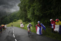 New overall leader Slovenia's Tadej Pogacar climbs Col de la Colombiere pass during the eighth stage of the Tour de France cycling race over 150.8 kilometers (93.7 miles) with a start in Oyonnax and finish in Le Grand-Bornand, France, on Saturday, July 3, 2021. (AP Photo/Christophe Ena)