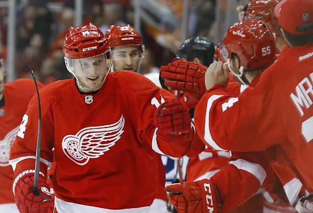 Detroit Red Wings center Gustav Nyquist (14), of Sweden, celebrates after scoring against the Toronto Maple Leafs in the third period of an NHL hockey game in Detroit, Tuesday, March 18, 2014. (AP Photo/Paul Sancya)