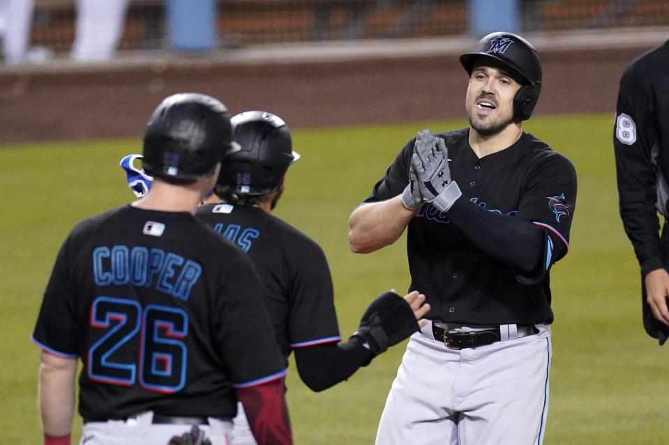 Miami Marlins' Adam Duvall, right, is congratulated by Miguel Rojas, center, and Garrett Cooper after hitting a three-run home run during the third inning of a baseball game against the Los Angeles Dodgers Friday, May 14, 2021, in Los Angeles. (AP Photo/Mark J. Terrill)