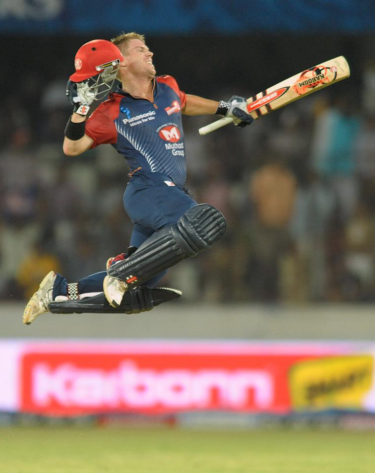 Delhi Daredevils batsman David Warner leaps in to air after scorong a century, 100 runs, during the IPL Twenty20 cricket match between the  Deccan Chargers and Delhi Daredevils at Rajiv Gandhi International Stadium in Hyderabad on May 10, 2012. RESTRICTED TO EDITORIAL USE. MOBILE USE WITHIN NEWS PACKAGE.  AFP PHOTO/ Noah SEELAM        (Photo credit should read NOAH SEELAM/AFP/GettyImages)
