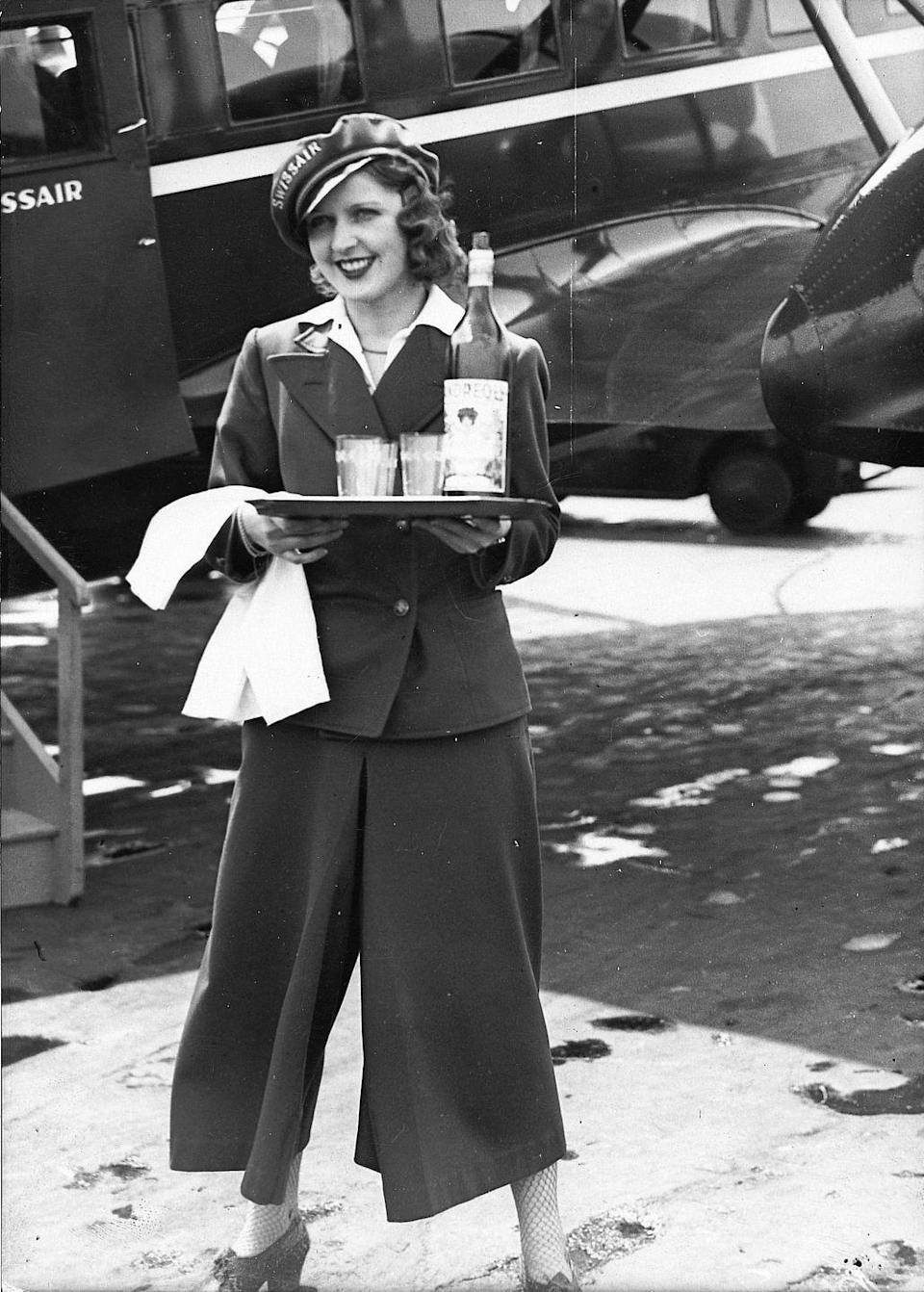 <p>In Europe, Candor Airlines was the first to employ a stewardess. A Swissair stewardess stands in front of a Condor aircraft at Tempelhof Airport in Berlin in 1934.</p>