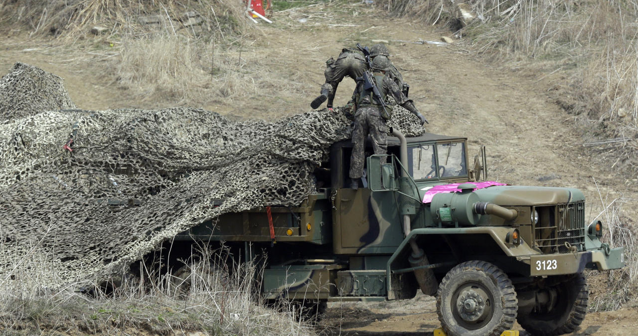 """South Korean soldiers place a camouflage net over their military vehicle during a military exercise near the border village of Panmunjom in Paju, north of Seoul, South Korea, Thursday, April 4, 2013. North Korea warned Thursday that its military has been cleared to attack the U.S. using """"smaller, lighter and diversified"""" nuclear weapons, while the U.S. said it will strengthen regional protection by deploying a missile defense system to Guam. (AP Photo/Lee Jin-man)"""