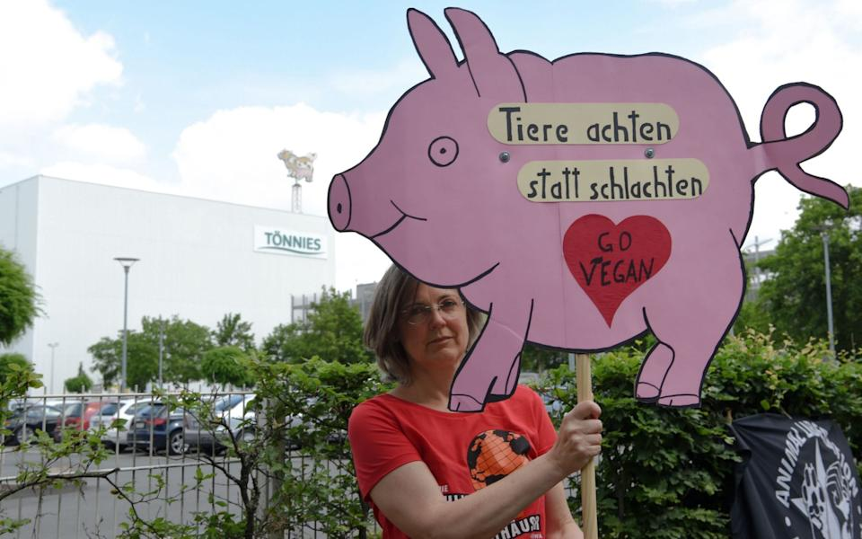 A demonstrator holds a sign that reads 'respecting animals instead of slaughtering them - go vegan' as she protests in front of the headquarters of abattoir company Toennies on June 20. The German army was there to establish a test center for the novel coronavirus. - Ina FASSBENDER / AFP