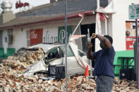 New Orleans Firefighters assess damages as they take photos and look through debris after a building collapsed from the effects of Hurricane Ida, Monday, Aug. 30, 2021, in New Orleans, La. (AP Photo/Eric Gay)