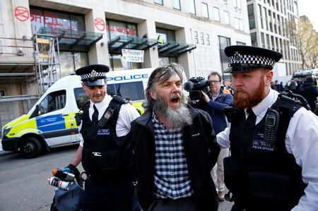 Police officers detain a climate change activist, during an Extinction Rebellion protest at the Shell Centre in London, Britain April 15, 2019. REUTERS/Henry Nicholls