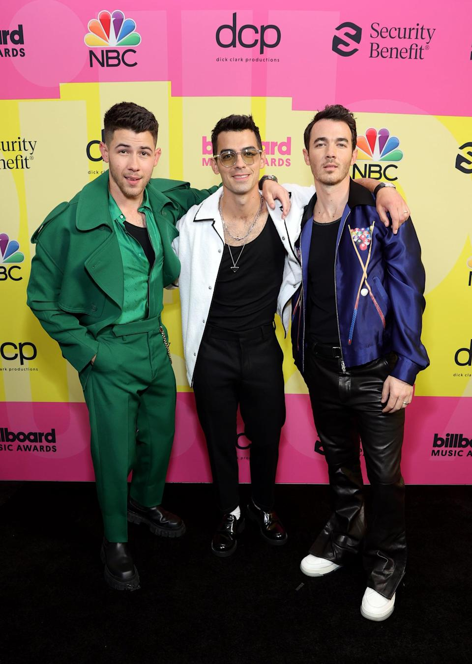<p>Nick wearing a green Fendi suit. Joe styling his Prada outfit with Cartier. Kevin wearing a purple bomber jacket and leather pants.</p>