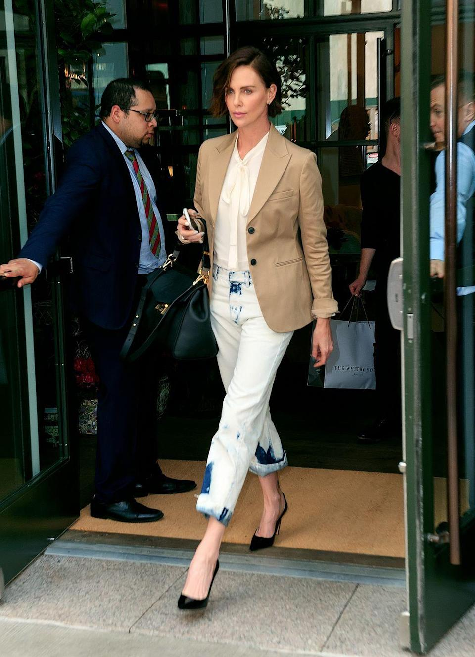 <p>It's easy to veer into fashion victim territory with acid washed denim, but Charlize Theron tones it down with a polished blazer and pointy-toe pumps.</p>