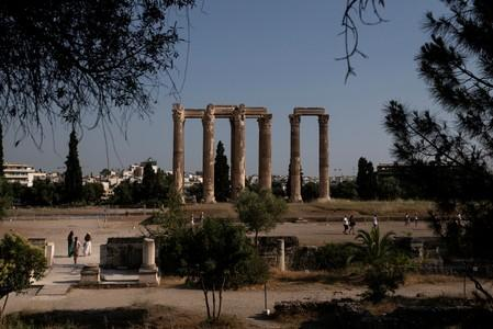 People visit the archaeological site of the ancient Temple of Zeus in Athens